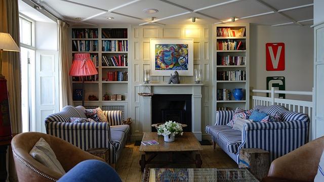 przytulny salon z kanapami i skórzanym fotelem z zagospodarowaną ścianą poprzez zamontowany kominek do mieszkania