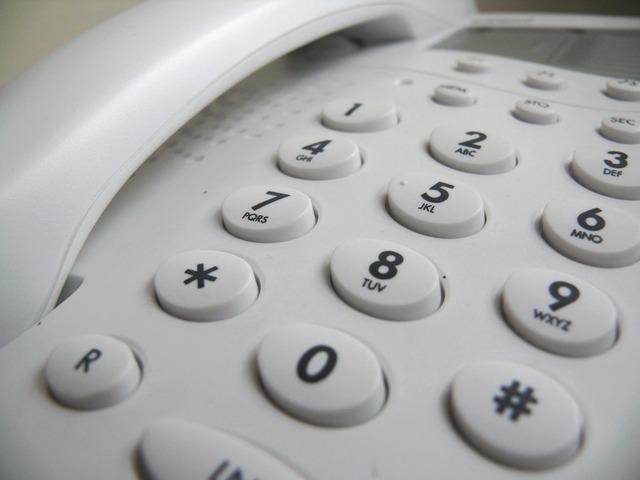 telefon stacjonarny na kartę z czarnymi cyframi na guzikach
