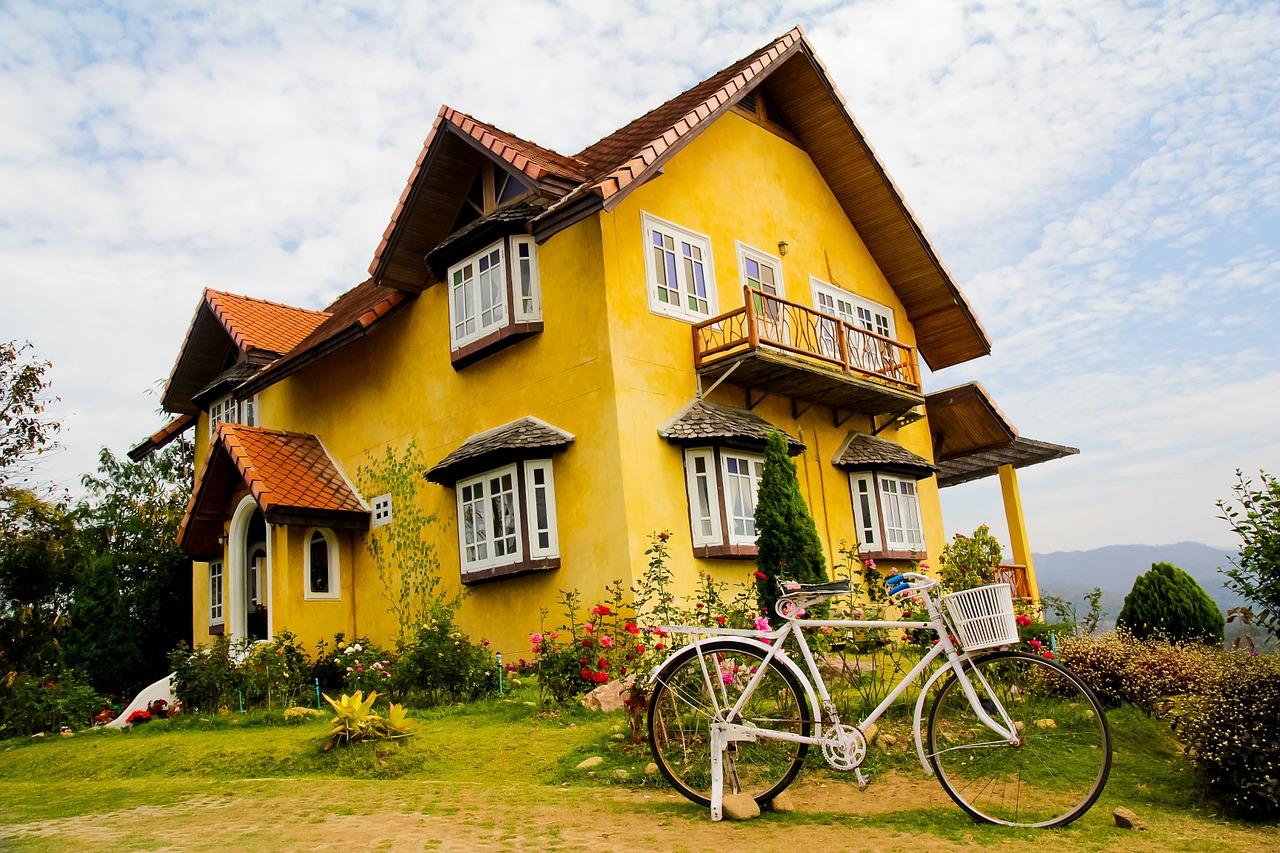 żółty piętrowy dom z ogłoszenia nieruchomości