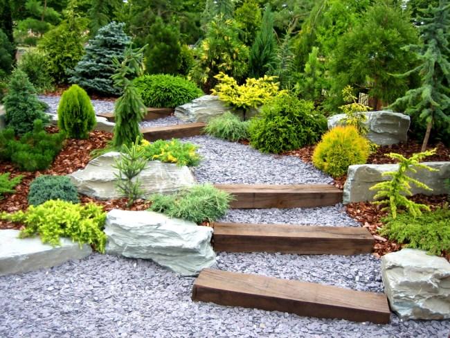 schody w ogrodzie w formie drewnianych belek nadaje stylu dróżce wysypanej szarym żwirem