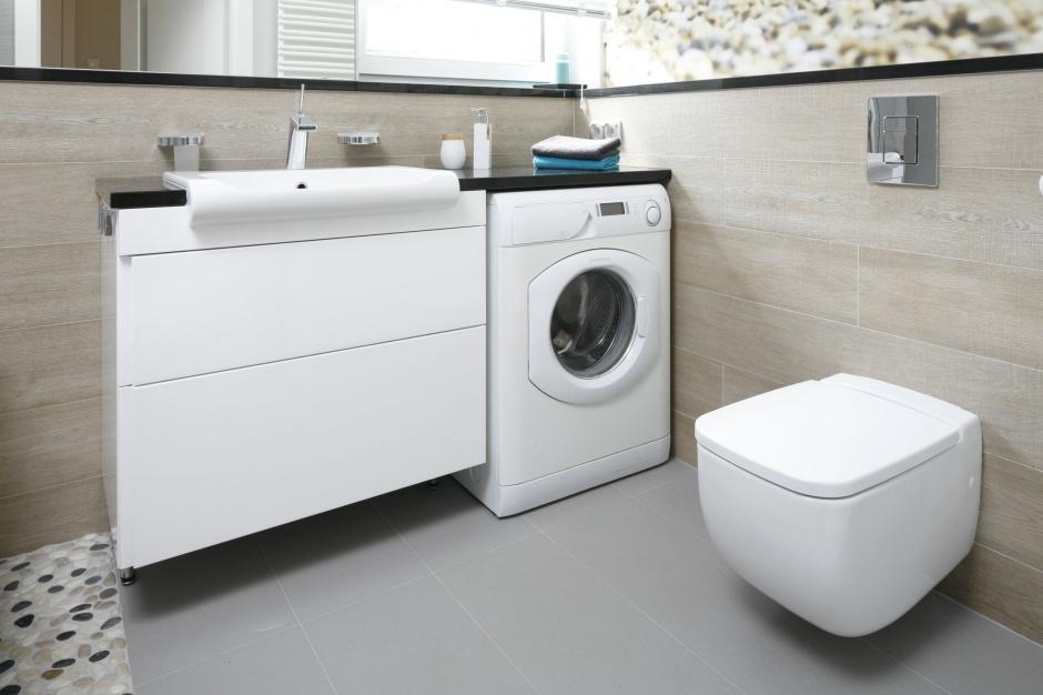 Pralka automatyczna w zabudowie w nowoczesnej łazience z podwieszaną szafką umywalkową i podwieszaną muszlą klozetową