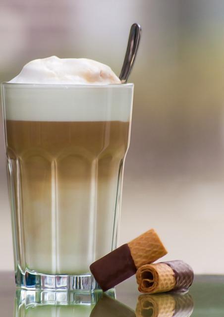latte z ekspresu automatycznego w towarzystwie waflowych ruloników w czekoladzie