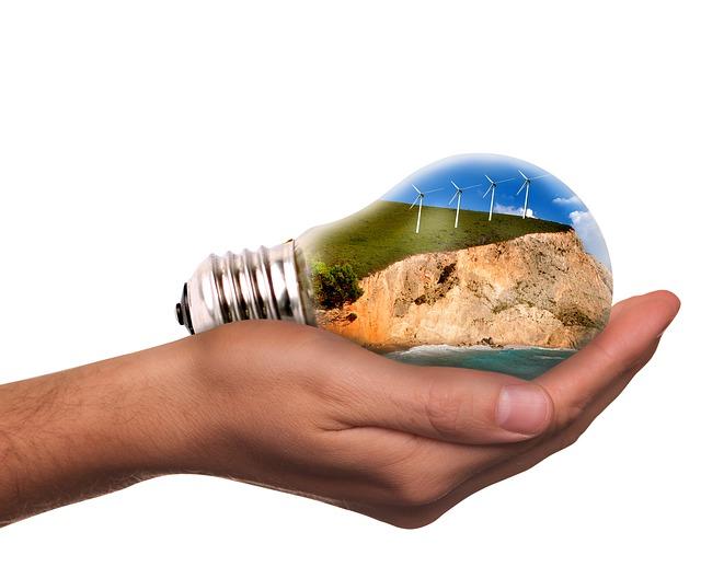 ekologia - żarówka na dłoni a w niej odnawialne źródło energii wiatraki